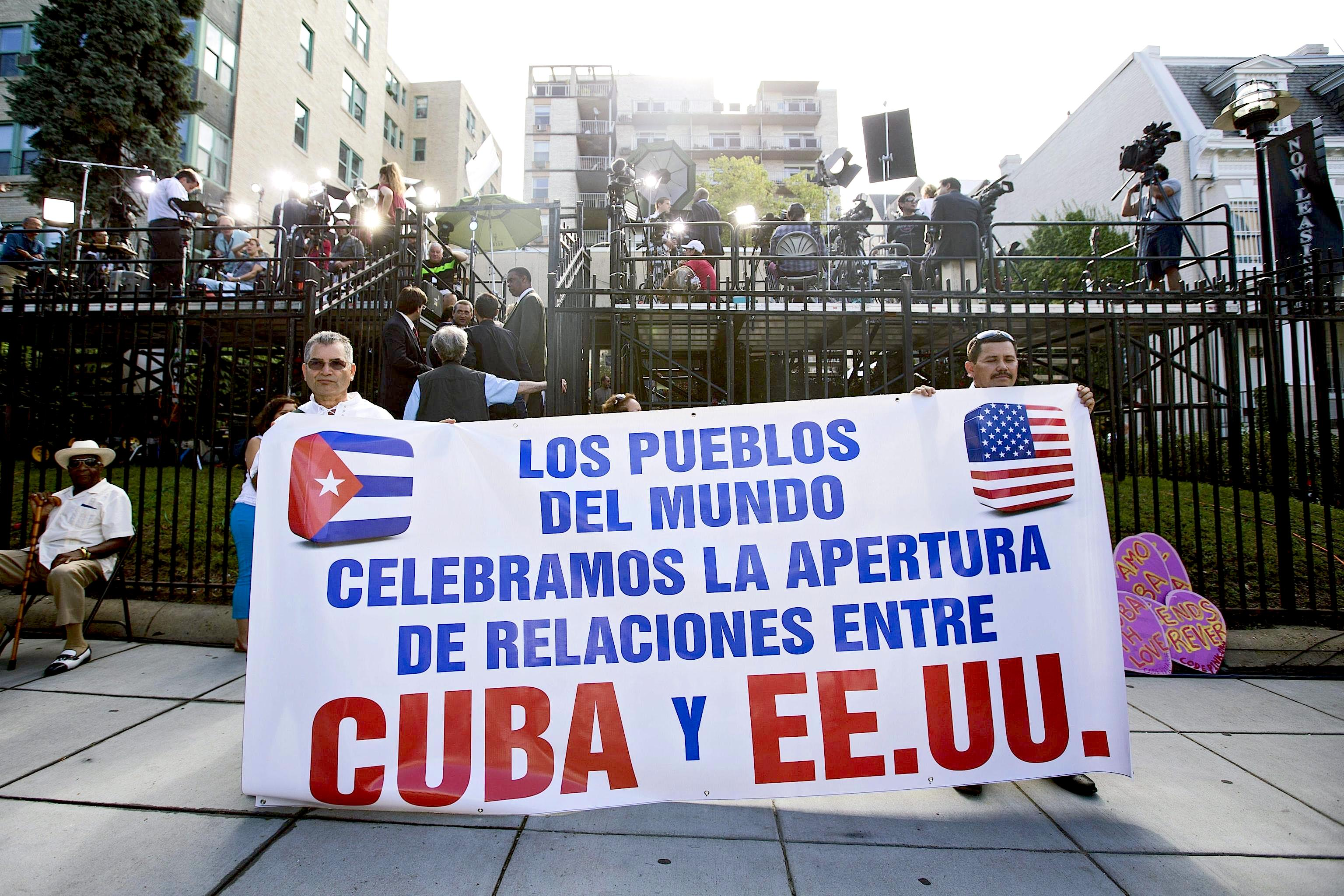 People show support for the re-establishment of US-Cuba relations with a banner reading 'The world's peoples celebrate the opening of relations -  20 July 2015.