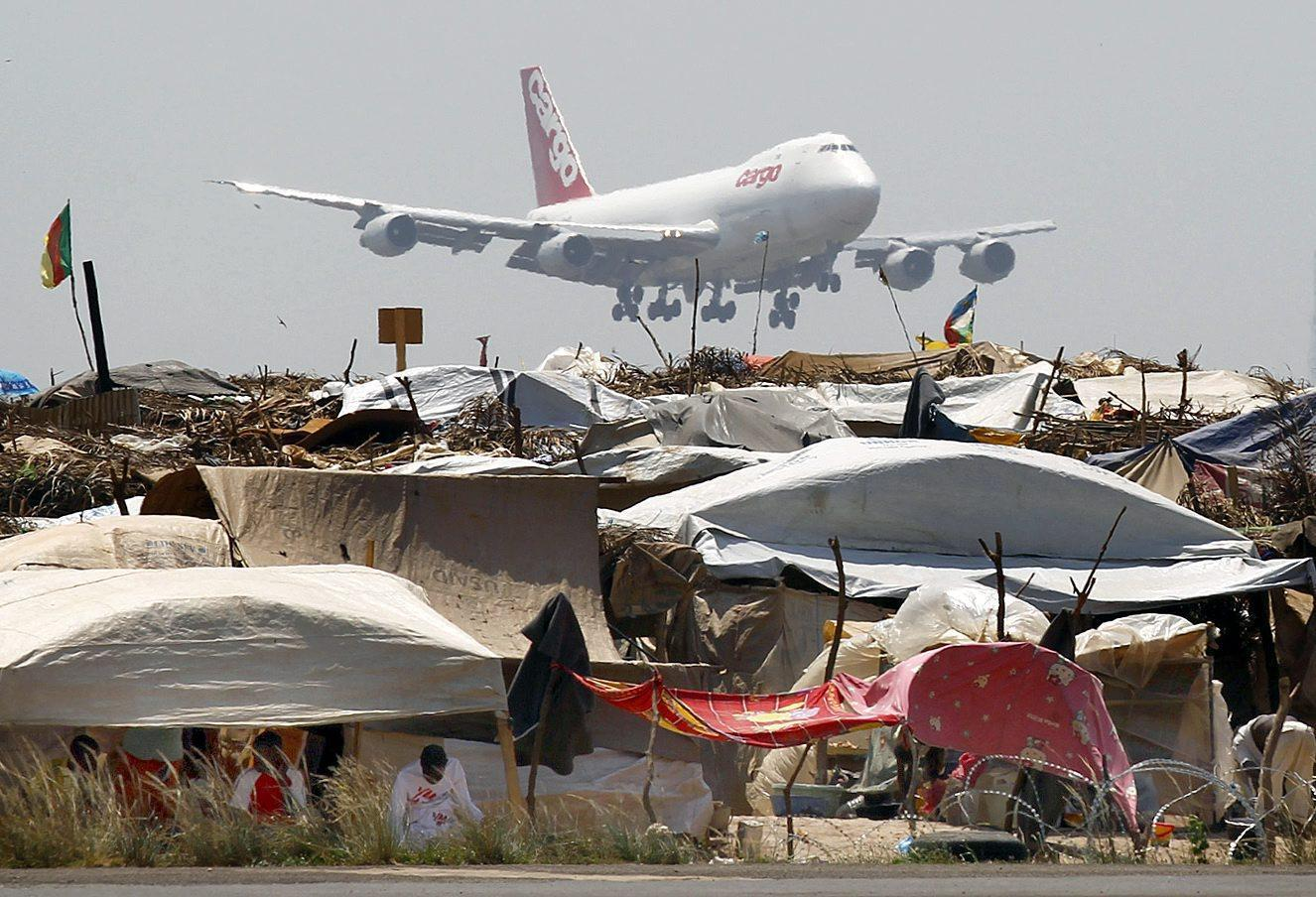 A cargo airplane of the World Food Programme (WFP) flies over a refugee camp for internally displaced persons as it touches down at the Airport of Mpoko