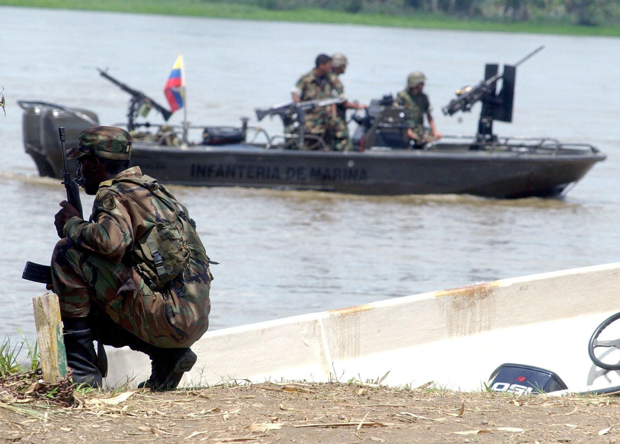 Colombian policemen patrol the Atrato River in Bojaya's jungle village of Choco Department