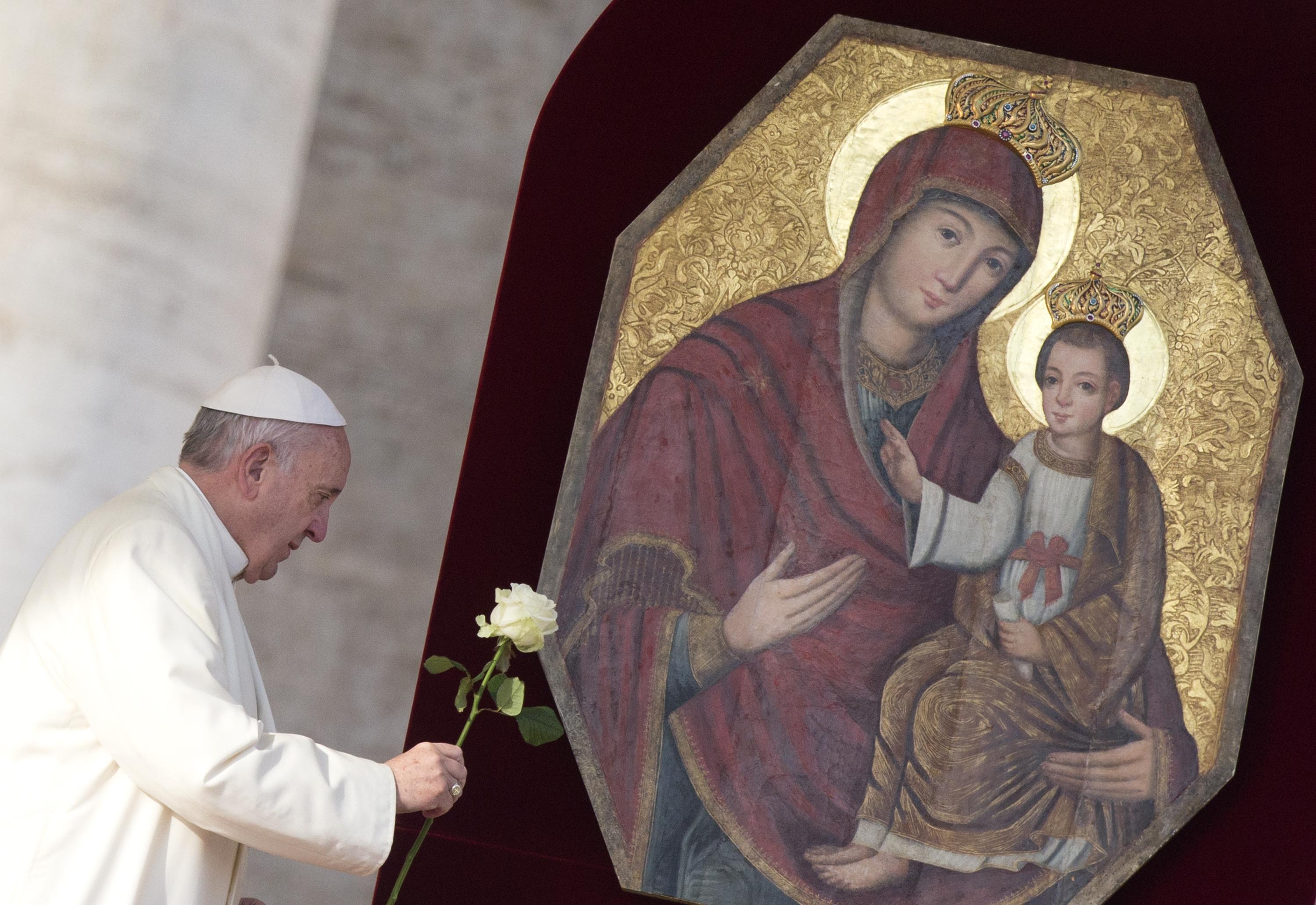 Pope Francis presents a rose at image of Holy Mary and Child Jesus prior his Wednesday General Audience