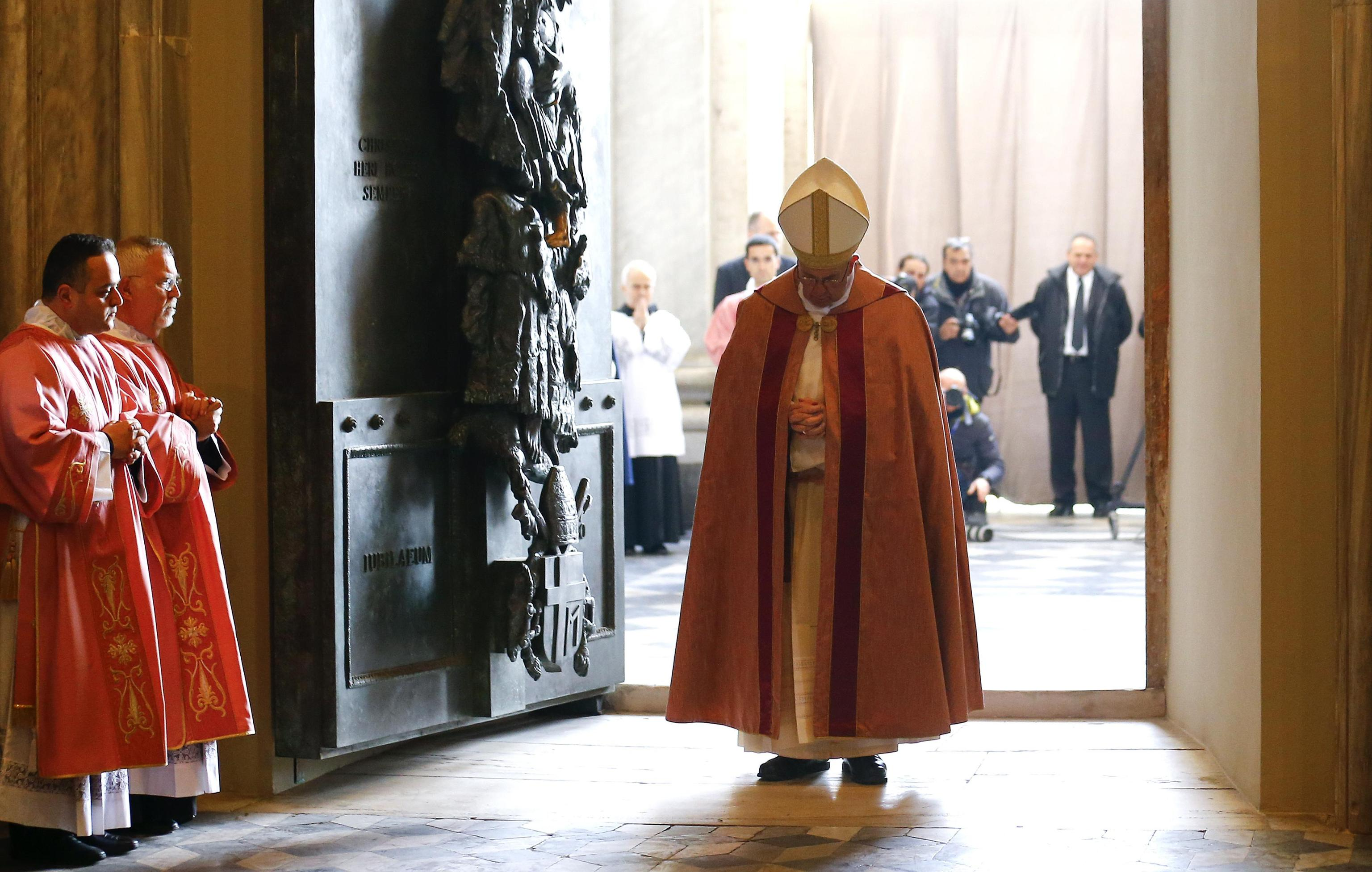 Pope Francis pauses and prays at the front of the Holy Door of the St John Lateran Basilica