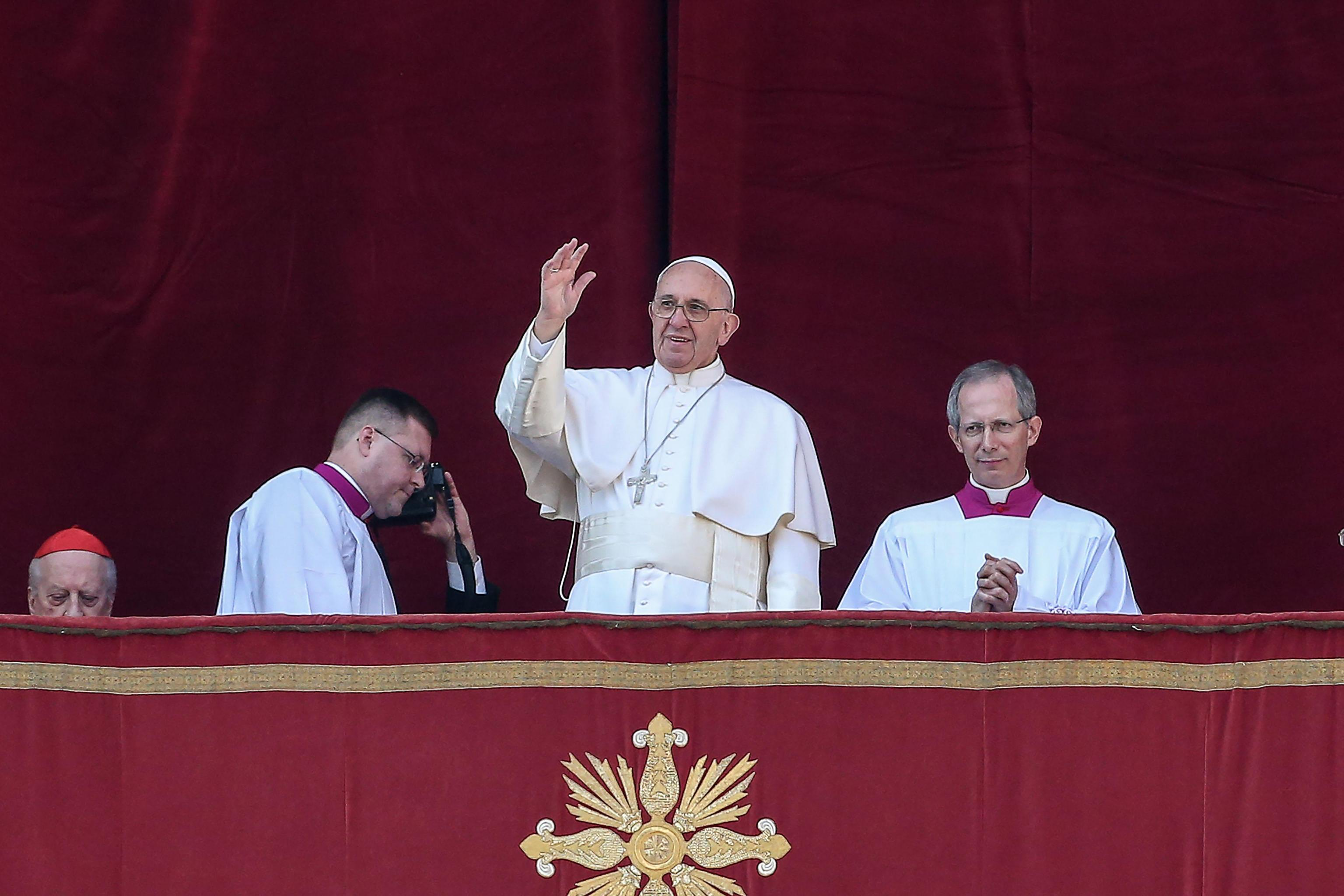 Pope Francis waves to the faithful as he delivers the traditional Urbi et Orbi Christmas Day message from the central balcony of St. Peters Basilica in Vatican City
