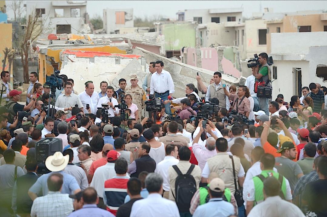 Mexican President Enrique Pena Nieto (C) speaking with inhabitants of Ciudad de Acuna after a tornado hit the city
