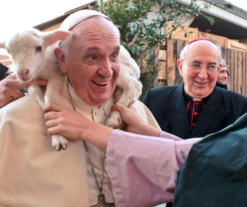 El Santo Padre visita un pesebre Romano, y le ponen un cordero sobre los hombros. (Foto copyright Osservatore Romano - 7 de enero 2014)