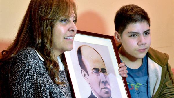 La señora Verónica y su hijo junto a la Foto del beato Miguez (Foto web iglesia.cl)