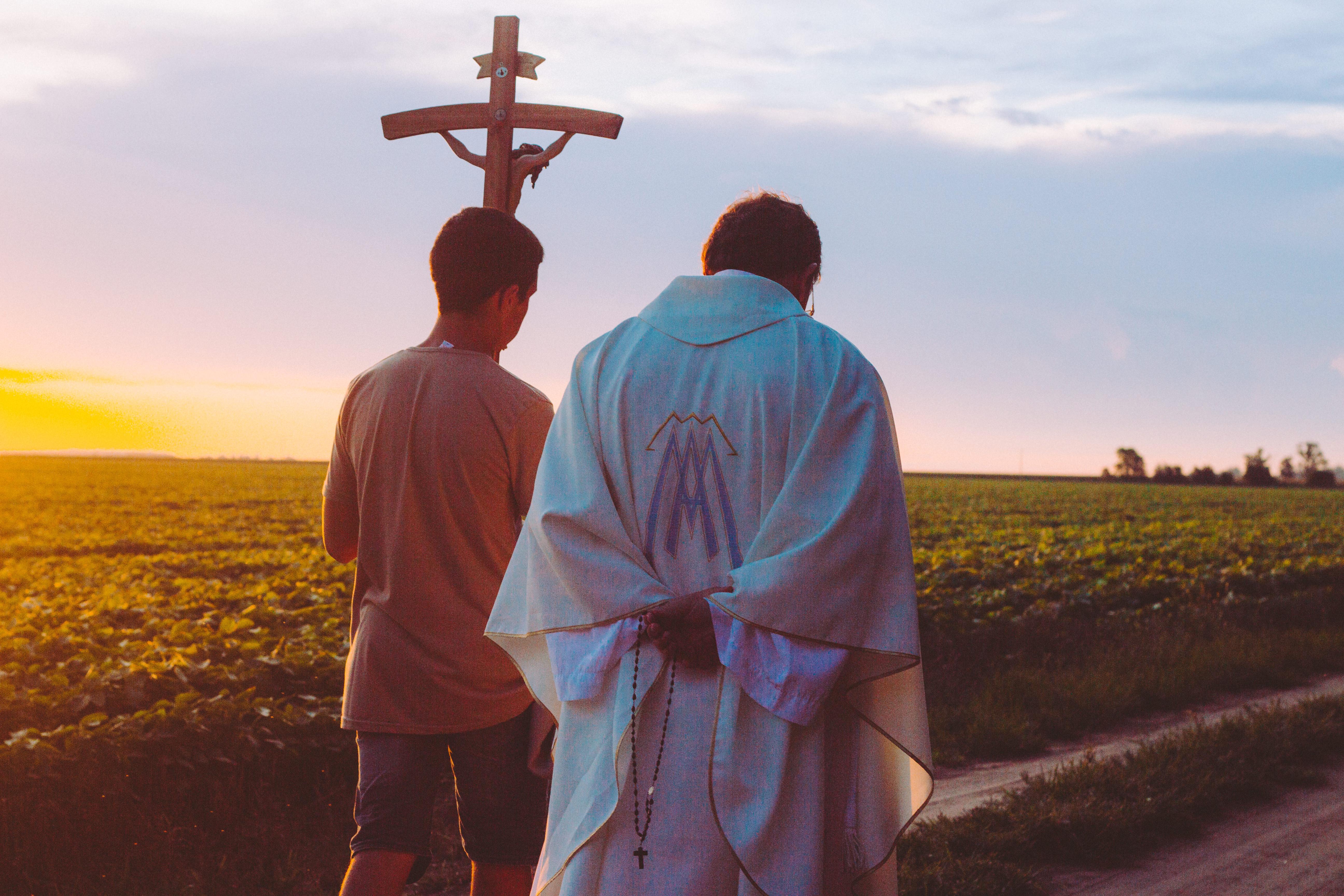 Un sacerdote habla con un chico joven © Cathopic