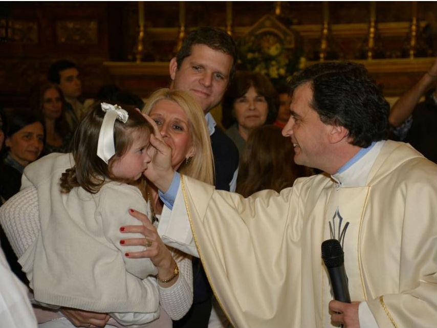 El P. Pablo Jourdan bendice a una niña © Facebook Parroquia Varela