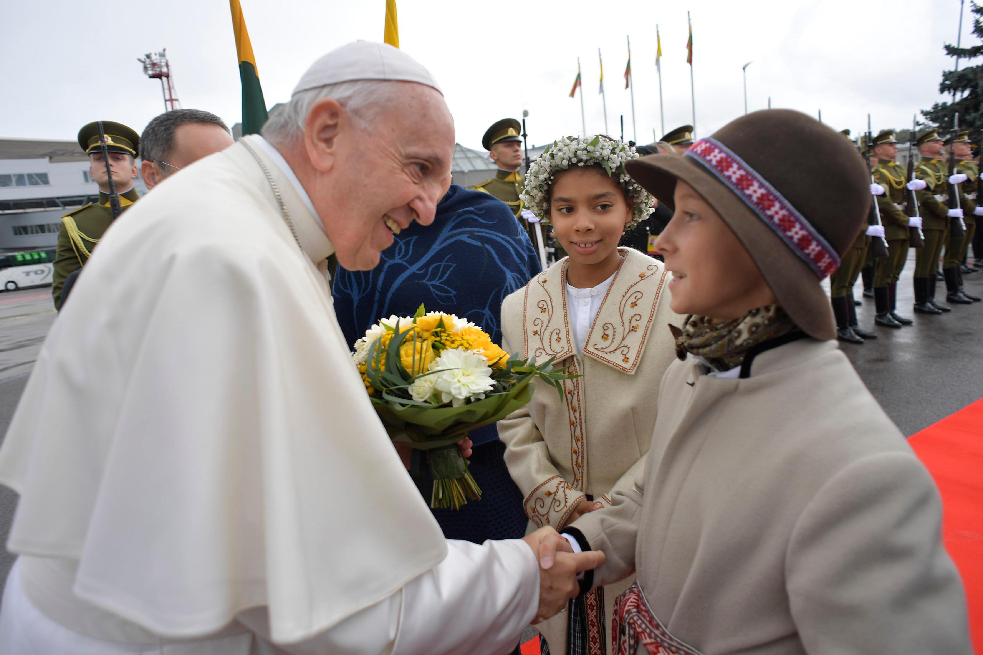 Dos niñas lituanas reciben al Papa con flores en el aeropuerto de Vilna © Vatican Media