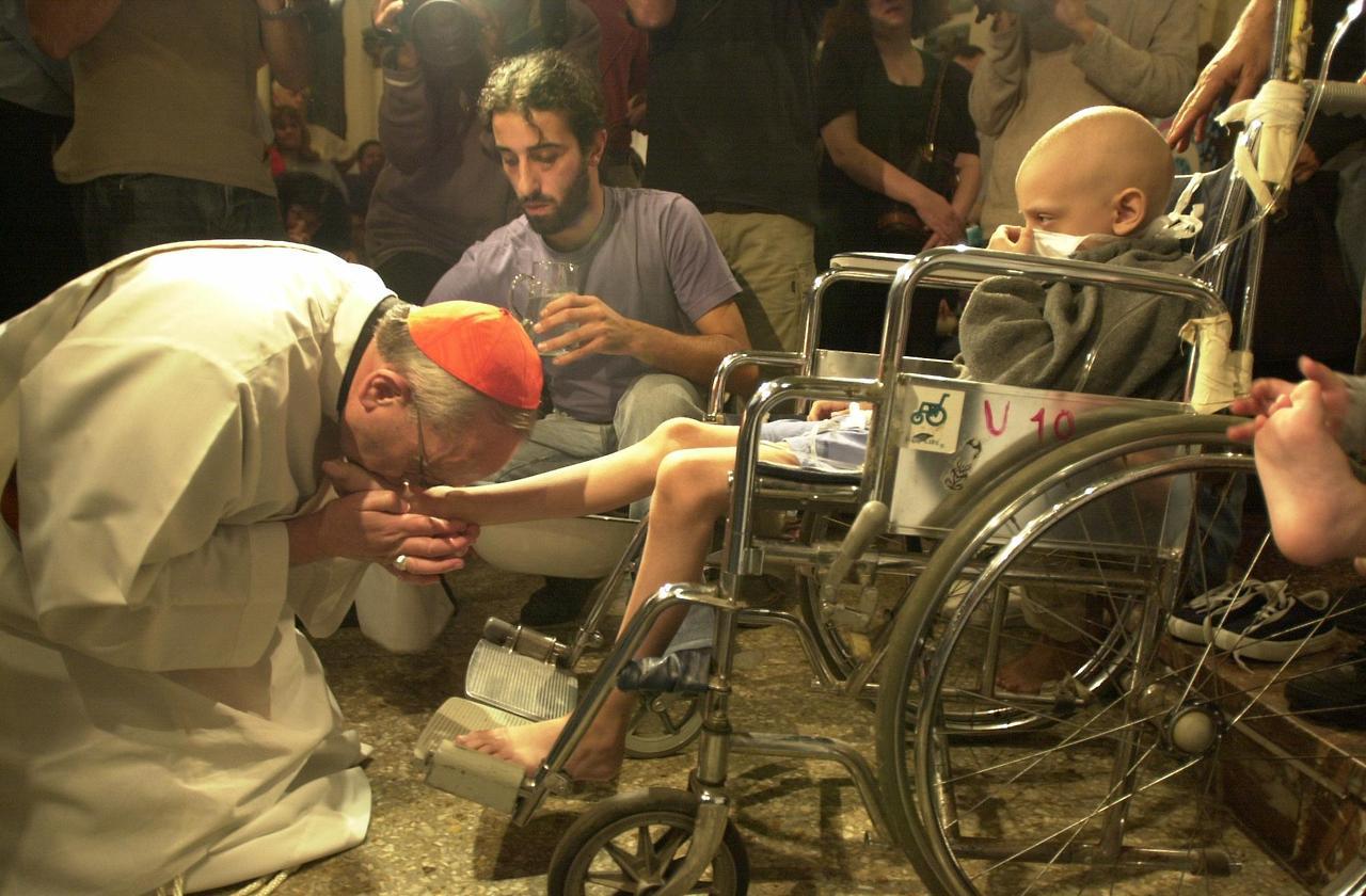 Cardenal Bergoglio besa los pies de un niño enfermo. Foto de archivo