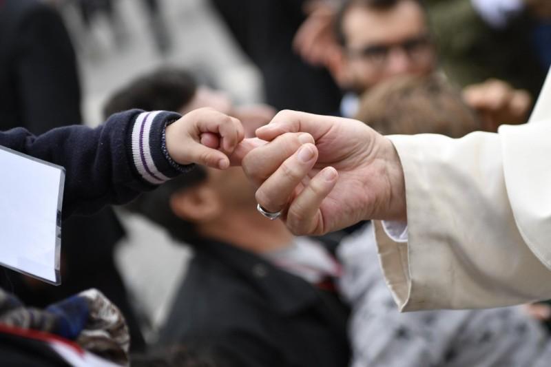 El Papa coge la mano de un niño © Vatican Media