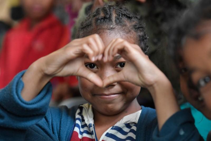 Una niña de Akamasoa hace un corazón © Vatican Media